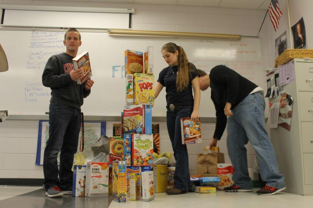 Senior Jordan Sollenberger and juniors Jackie Williams and Landon Holley help stack up the cereal boxes that were collected in partnership with FFA to help feed the homeless at House of Hope.