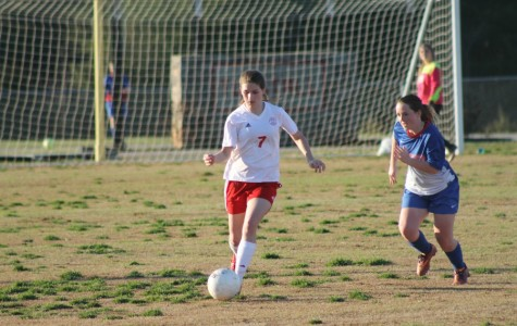 Lexi Toufas, sophomore, dribbles by Wildcat attacker.
