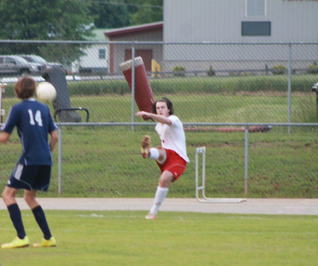 Senior Greyson Cooke executing a corner kick.