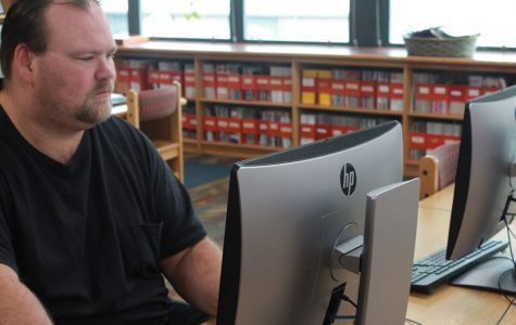 Bobby Clowers working hard to fix a computer in the library.