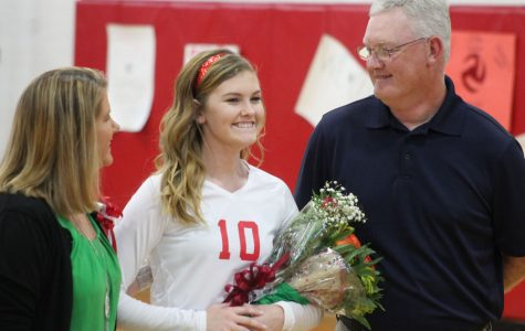 After shaking her coach's and principal's hands, Abby Scarce stands with her parents as she is recognized.
