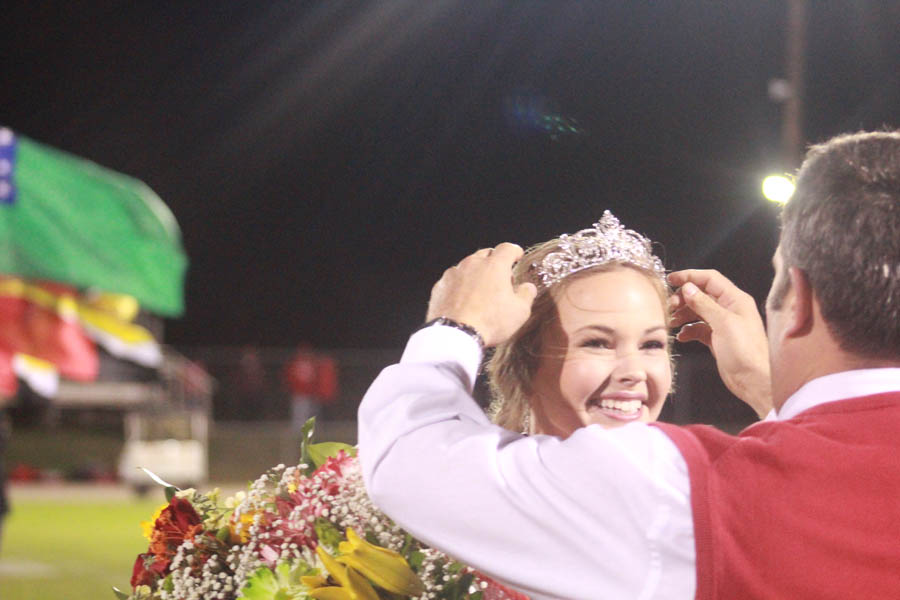 Holly receives her crown from principal Brian Boles.