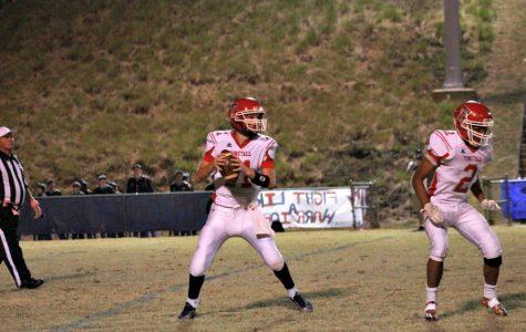 Trojans quarterback Luke Buckner (11) looks for an open receiver while running back Trevor Lovelace (2) looks for a man to block