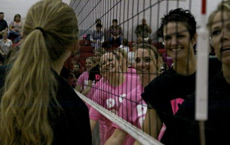 The varsity volleyball team and the alumni wishing each other good luck before the game begins.