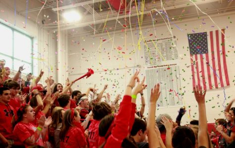 The senior class throwing confetti into the air while chanting