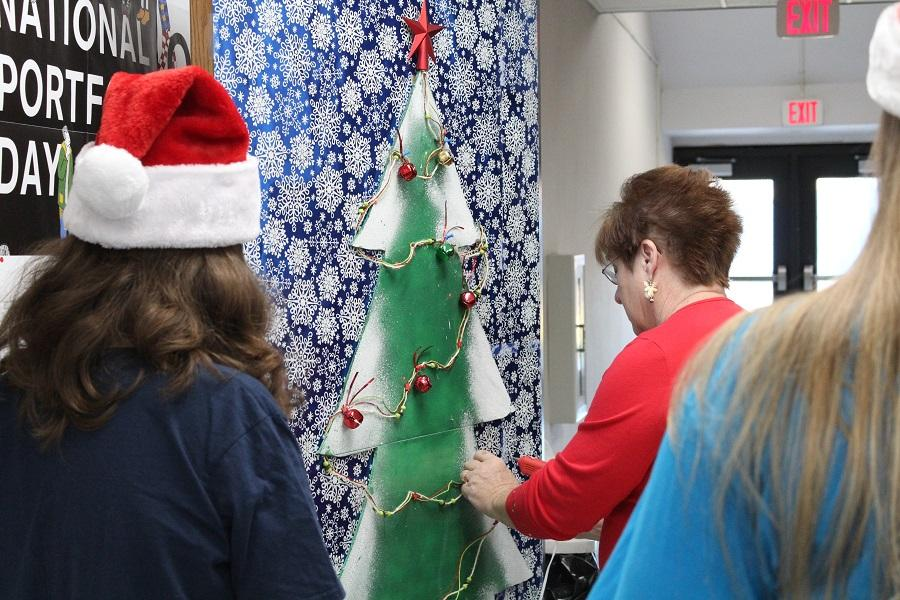Mrs. Evans and few art students decorate their door for Deck the Halls.