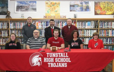 McBride signs his Letter of Intent to play college football this upcoming fall with family, coaches, and Principal Bowles supporting him
