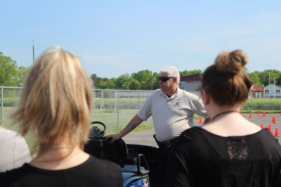 Deputy Silverman talks to students in a Driver's Ed class before they participate in a drunk driving simulation with a golf cart.