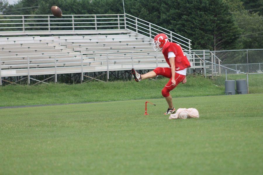 Senior Zach Mensavage practicing kicking and punting