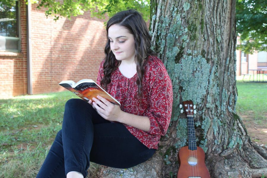 Kacey taking a break from school and reading outside