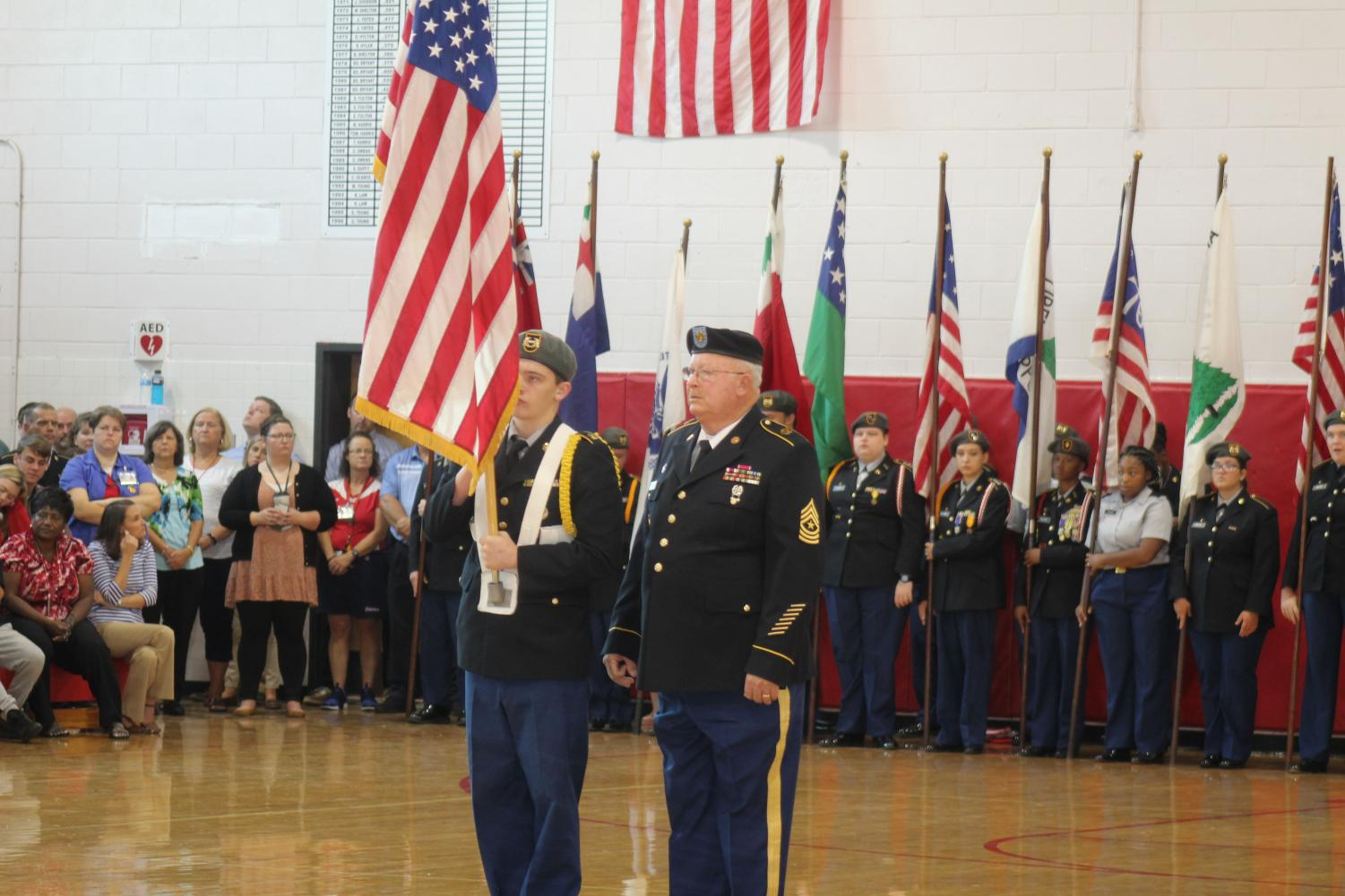 Junior Brandon Day presenting the United States of America flag accompanied by Sgt. Major Hubert Royall.