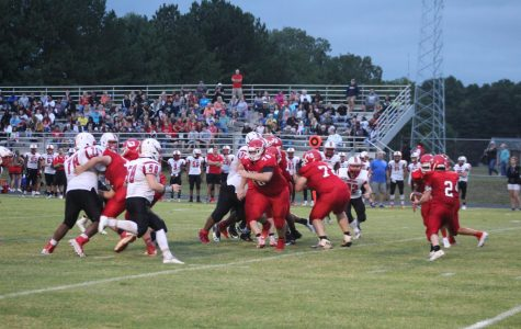 The Trojan football team looks to run the ball against rival Chatham.