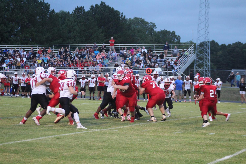 The Trojan football team looks to run the ball against rival Chatham.