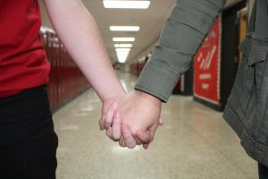 Two students holding each others hand in an empty school hallway.