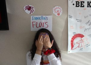Junior Daniella Espinoza standing under drawings that represent her fears.