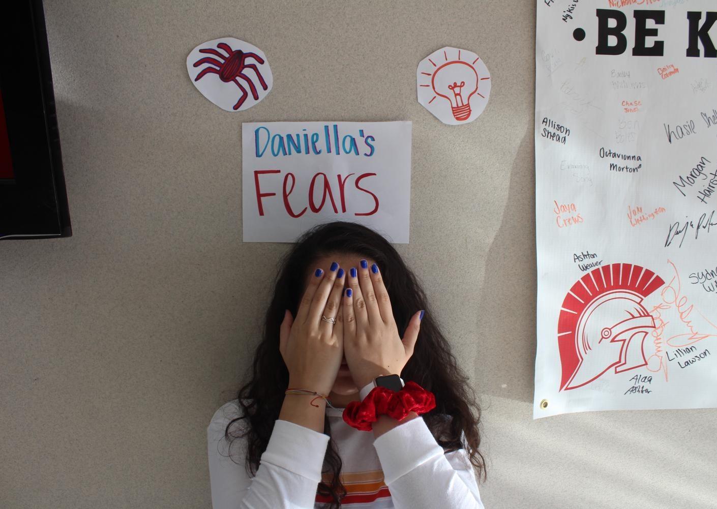 Junior Daniella Espinoza standing under drawings that represent her fears.