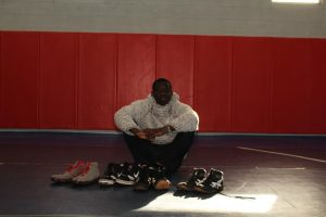 Jhalin Godwin sitting on the wrestling mat with his shoes.