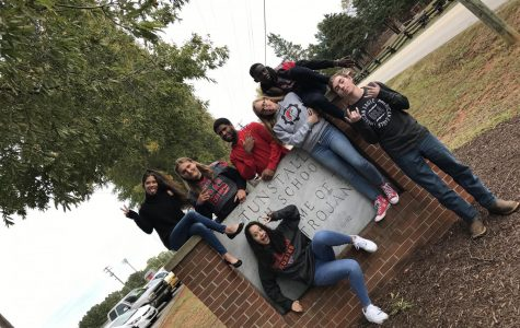 The 2019-2020 Trojan Messenger sign posing in front of Tunstall High School sign.